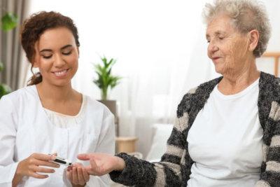 nurse checking elder woman's glucose level