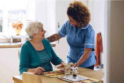 caregiver giving elder woman a meal