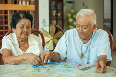 elderly couple playing with a jigsaw puzzle